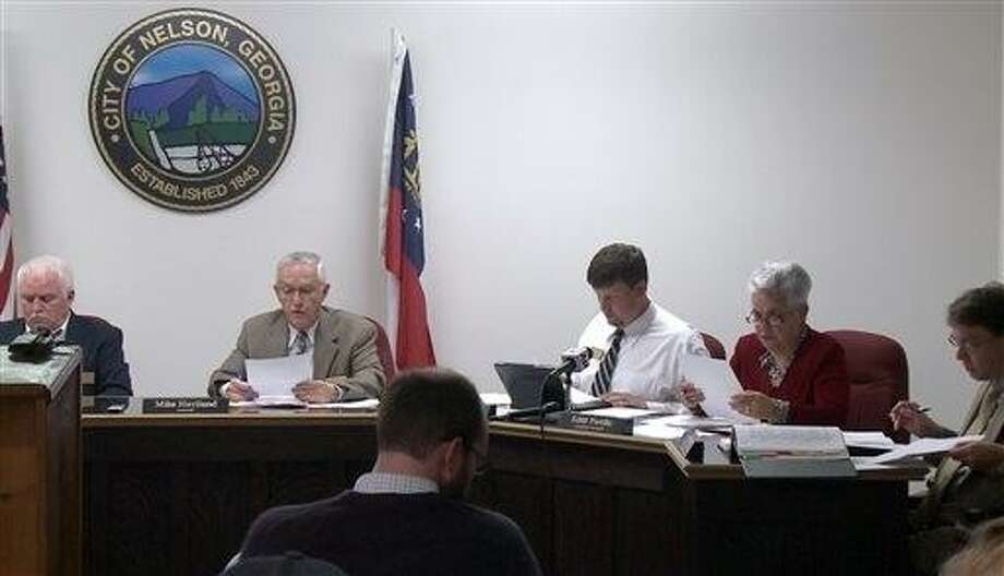 """In a this image made from video, the Nelson, Ga. City Council meets to vote on a mandatory gun ownership ordinance for all heads-of-household, Monday, April 1, 2013. From left are council member Jackie Jarrett, Mayor Mike Haviland, council member Duane Cronic, council member Edith Portillo, and city attorney Jeff Rusbridge. Council members in Nelson, a city of about 1,300 residents that's located 50 miles north of Atlanta, voted unanimously to approve the Family Protection Ordinance. The measure requires every head of household to own a gun and ammunition to """"provide for the emergency management of the city"""" and to """"provide for and protect the safety, security and general welfare of the city and its inhabitants."""" (AP Photo/Johnny Clark) Photo: AP / AP"""