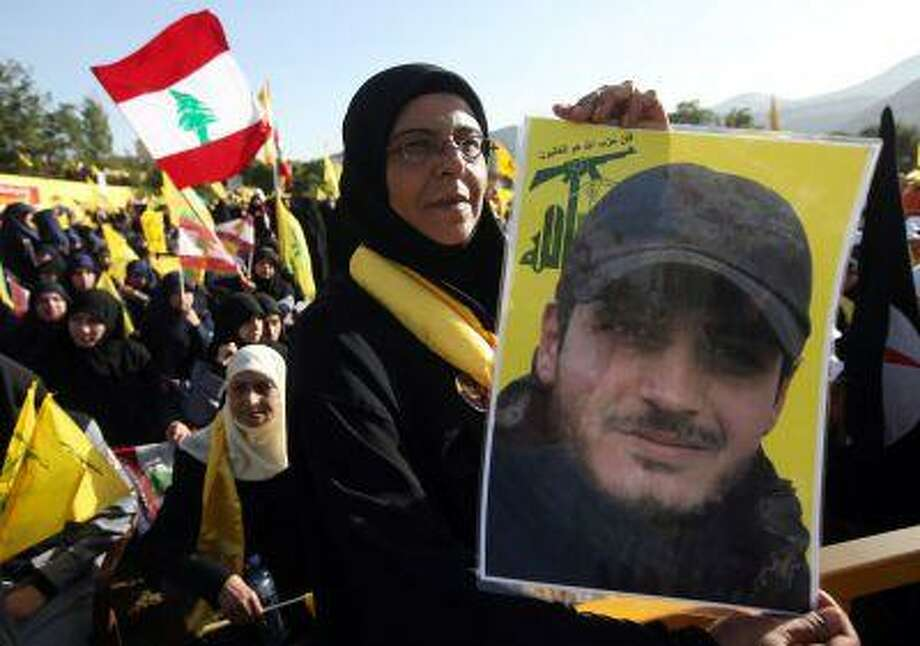 A Hezbollah supporter holds a portrait of her son, Ibrahim Kanso, 24, who was killed during a battle in Syria against the Syrian rebels. Photo: ASSOCIATED PRESS / AP2013