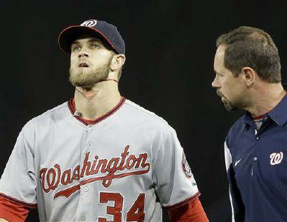 Washington Nationals right fielder Bryce Harper, bleeding from an injury to his neck, walks to the dugout with trainer Lee Kuntz after hitting the right field wall wall, chasing a triple off A.J. Ellis of the Los Angeles Dodgers in the fifth inning of a baseball game in Los Angeles May 13, 2013. Photo: AP / AP