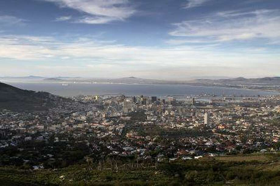 The city skyline of Cape Town is seen from Table Mountain in Cape Town, South Africa; Cape Town is bordered by two oceans and one mountain range and is the rare city that abuts actual wilderness.