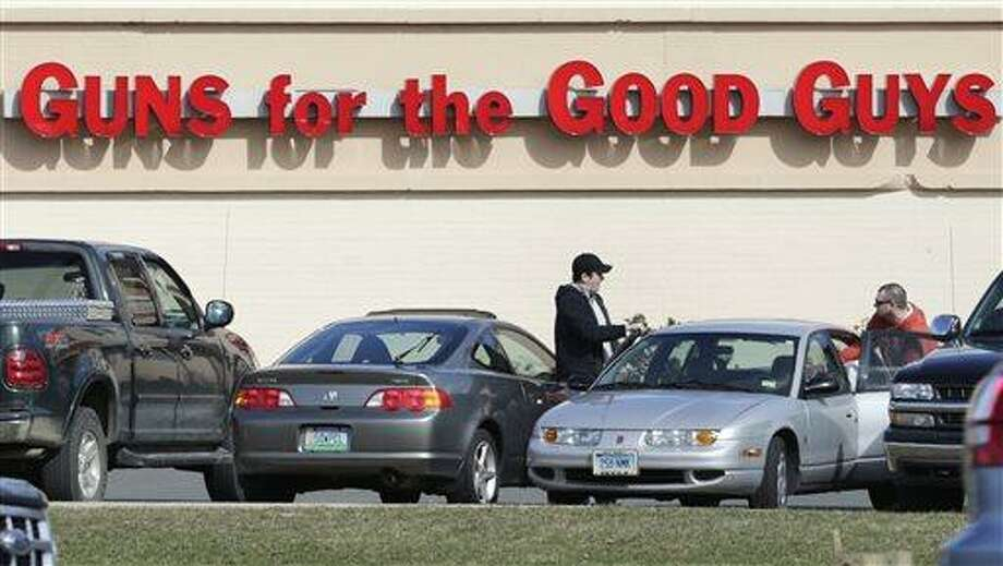 Shoppers leave Hoffman's Gun Center with their purchases in Newington, Conn., Tuesday, April 2, 2013. Customers are packing gun stores around Connecticut following the unveiling of new gun-control legislation, which could take effect as soon as Wednesday evening. (AP Photo/Charles Krupa) Photo: AP / AP