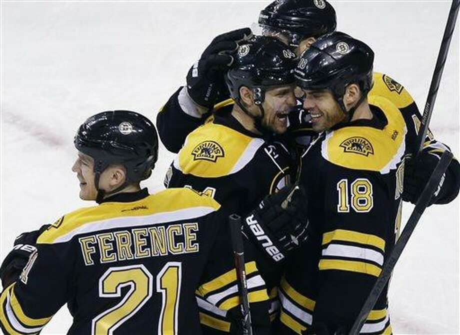 Boston Bruins right wing Nathan Horton (18) celebrates his goal with defensemen Dennis Seidenberg, center left, and Andrew Ference (21) in the third period of an NHL hockey game against the Ottawa Senators in Boston, Tuesday, April 2, 2013. The Bruins won 3-2. (AP Photo/Elise Amendola) Photo: ASSOCIATED PRESS / AP2013