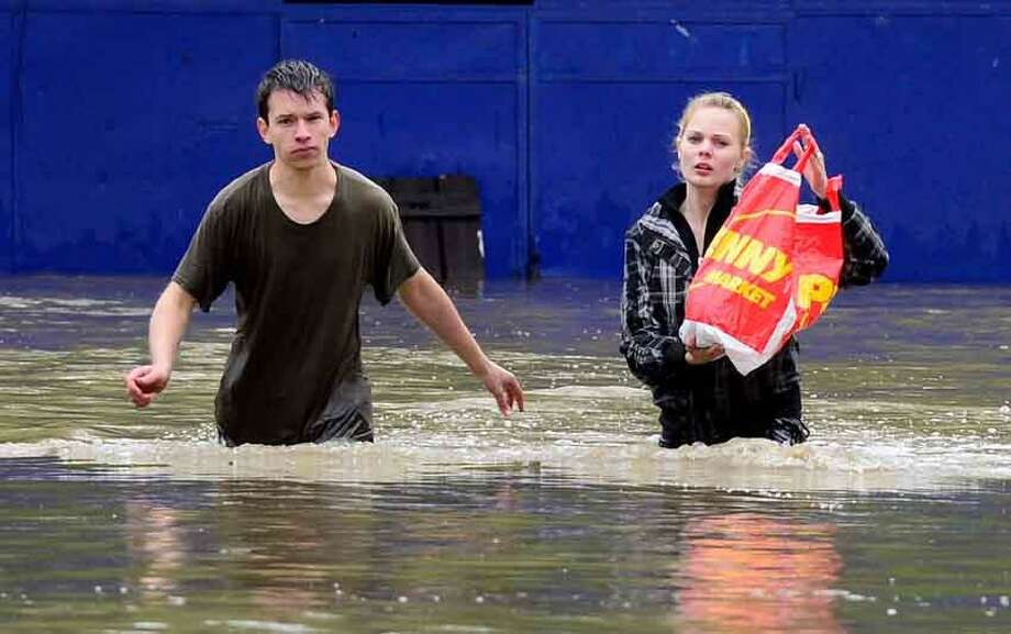 The Sunday, June 2, 2013 photo shows a couple trying to save three small kittens hidden in a plastic bag, which were endangered by a swollen Botic creek in Pragueís suburb Zabehlice, Czech Republic, on Sunday, June 2, 2013. (AP Photo/CTK, Roman Vondrous) Photo: AP / CTK
