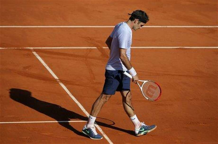 Switzerland's Roger Federer walks on the court as he plays France's Jo-Wilfried Tsong74during their quarterfinal match of the French Open tennis tournament at the Roland Garros stadium Tuesday, June 4, 2013 in Paris. Tsonga won 7-5, 6-3, 6-3. (AP Photo/Michel Spingler) Photo: ASSOCIATED PRESS / AP2013