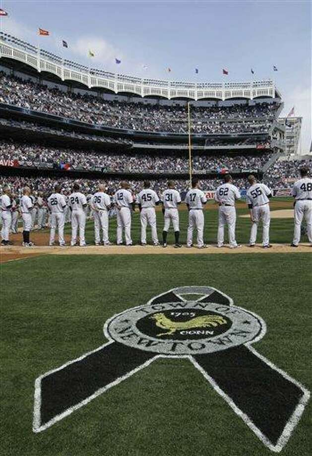 A logo dedicated to the town of Newtown,  Connecticut, is painted on the grass as players line up during an honor guard and tribute to the Newtown school shooting victims at an Opening Day baseball game at Yankee Stadium in New York, Monday, April 1, 2013.  (AP Photo/Kathy Willens) Photo: AP / AP