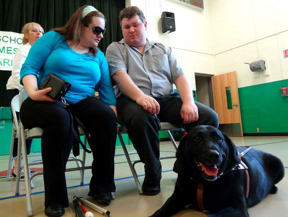 Bernadetta Pracon, Cameron Strife and Twain the guide dog arrives at Bradley Elementary School to share their experiences with the children. Darren Yip/For the Register