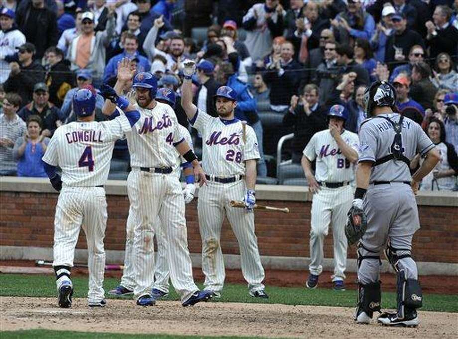 San Diego Padres catcher Nick Hundley (4) watches New York Mets' John Buck (44) and Daniel Murphy (28) greet Collin Cowgill (4) at home plate after Cowgill hit a grand slam home run off Padres relief pitcher Brad Brach that scored Buck, Reuben Tejada and Jordany Valdespin in the seventh inning on Opening Day of a baseball game at Citi Field on Monday, April 1, 2013 in New York. The Mets won 11-2. (AP Photo/Kathy Kmonicek) Photo: AP / FR170189 AP