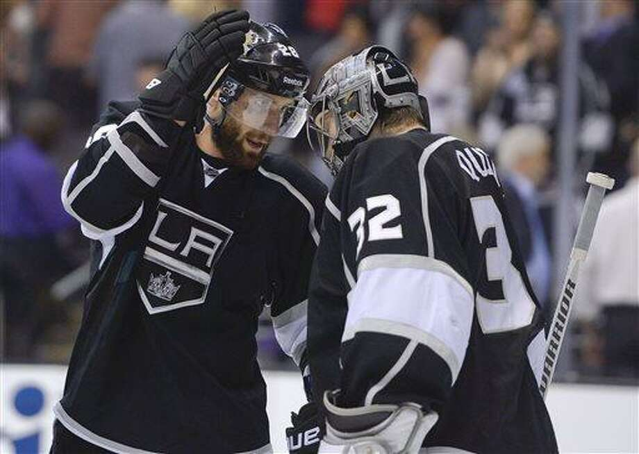 Los Angeles Kings center Jarret Stoll (28) congratulates goalie Jonathan Quick (32) after the Kings defeated the Chicago Blackhawks 3-1 in Game 3 of the NHL hockey Stanley Cup playoffs Western Conference finals, Tuesday, June 4, 2013, in Los Angeles. (AP Photo/Mark J. Terrill) Photo: AP / AP