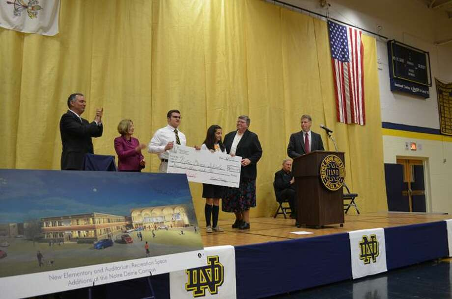 Rachel Murphy/Rome Observer Sr. Ann Mae Collins, principal of Notre Dame Jr./Sr. High School accepts a $4 million check towards the Capitol Campaign from the Good News Foundation of Central New York on Tuesday during a press conference.