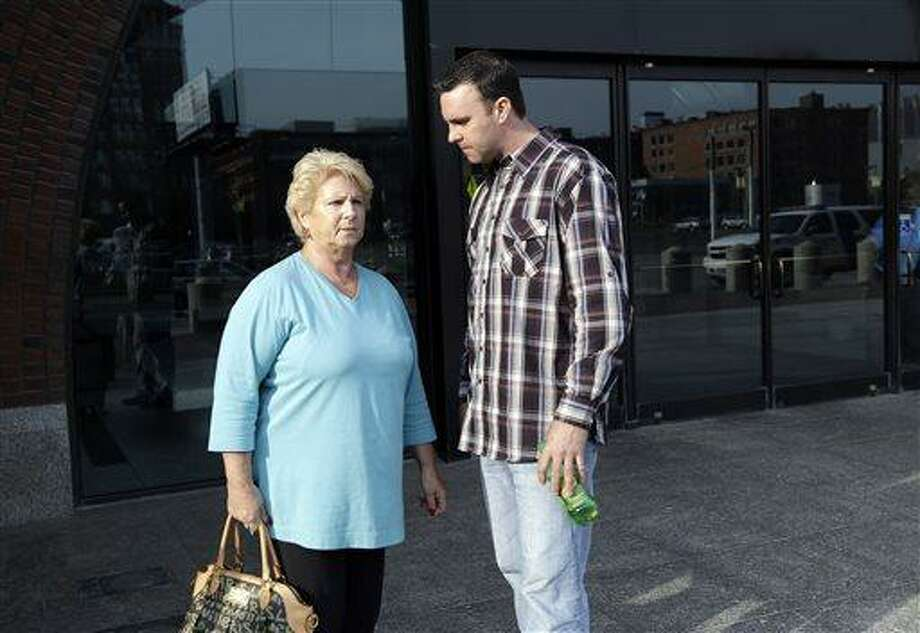 """Patricia Donahue, widow of alleged murder victim Michael Donahue, stands with her son, Tommy, outside federal court in Boston, Monday, June 3, 2013, after a pre-trial hearing for accused mobster James """"Whitey"""" Bulger. Jury selection begins Tuesday. (AP Photo/Elise Amendola) Photo: AP / AP"""