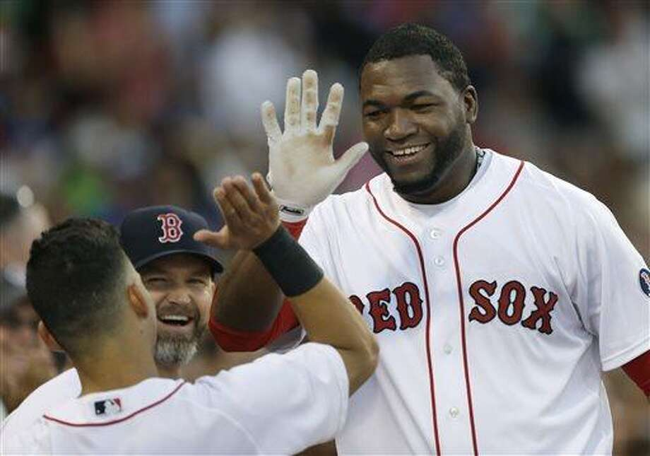 Boston Red Sox designated hitter David Ortiz celebrates at the dugout after he scored on a sacrifice fly by Mike Napoli against the Texas Rangers during the second inning of a baseball game at Fenway Park in Boston, Tuesday, June 4, 2013. (AP Photo/Elise Amendola) Photo: AP / AP