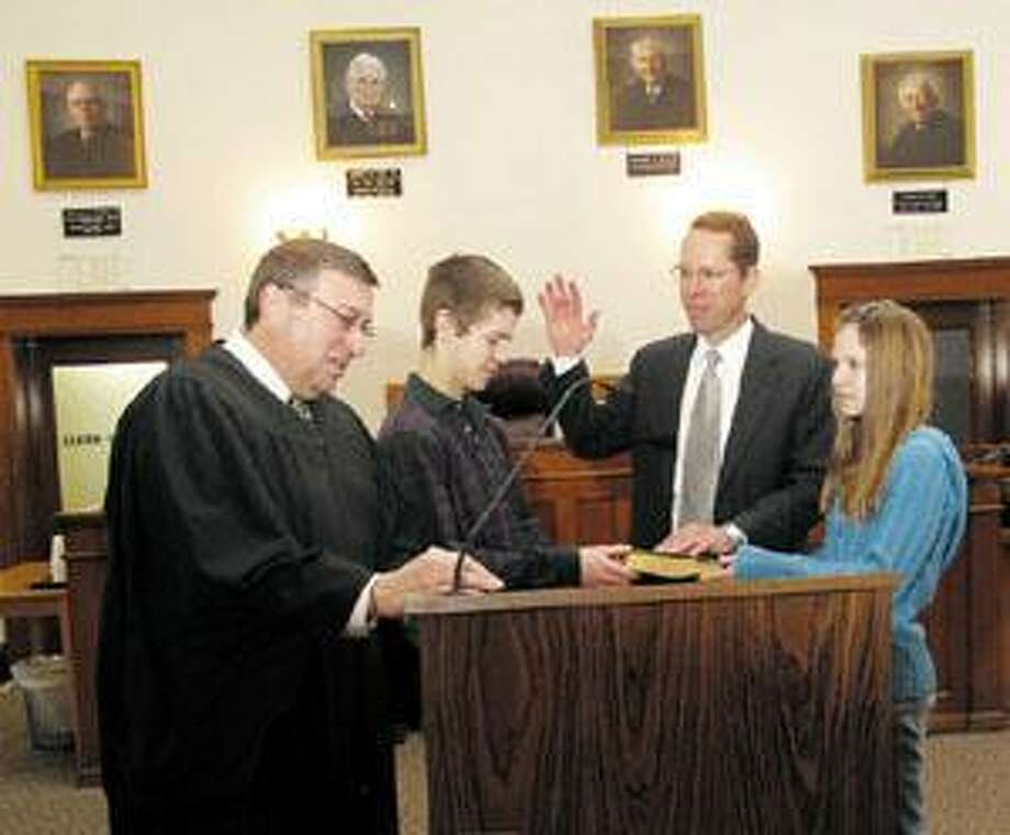 Photo by JOHN HAEGER Madison County Judge Biagio DiStefano administers the oath of office to Madison County DA Bill Gabor in January, 2009. Gabor's children are holding the Bible.