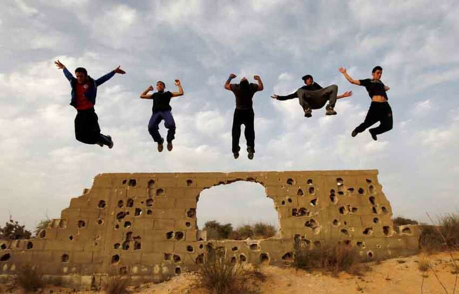 Palestinian youths practice their parkour skills in KhanYounis, southern Gaza Strip , Sunday, March 31, 2013. Parkour is a physical discipline of movement focused on overcoming obstacles. Training is held at cemeteries in KhanYounis. (AP Photo/Hatem Moussa) Photo: ASSOCIATED PRESS / THE ASSOCIATED PRESS2013