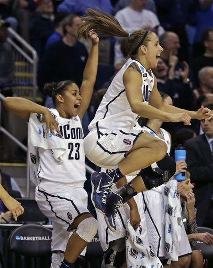 Connecticut guard Caroline Doty, right, leaps in the air as she celebrates with teammate Kaleena Mosqueda-Lewis (23) in the final seconds of the second half of a women's NCAA regional final basketball game against Kentucky in Bridgeport, Conn., Monday, April 1, 2013. Connecticut won 83-53 and advances to the Final Four. (AP Photo/Charles Krupa) Photo: ASSOCIATED PRESS / AP2013