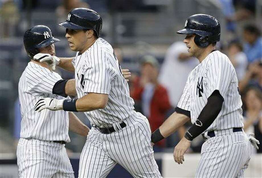 New York Yankees' Brett Gardner, left, and Austin Romine, right, celebrate with Mark Teixeira after Texeira's third-inning grand slam off Cleveland Indians starting pitcher Justin Masterson in a baseball game at Yankee Stadium in New York, Monday, June 3, 2013. (AP Photo/Kathy Willens) Photo: AP / AP