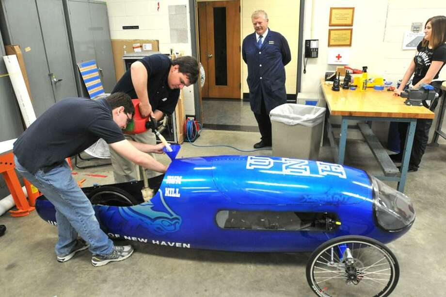 """West Haven--Seniors Daniel Bennett, left, and Joseph Olenick fill the fuel tank on the supermilage car built by the engineering department at UNH. The vehicle, which gets 800+ mpg will compete in an international contest in Marshall Michigan later in the week. Photo-Peter Casolino/Register <a href=""""mailto:pcasolino@newhavenregister.com"""">pcasolino@newhavenregister.com</a>"""