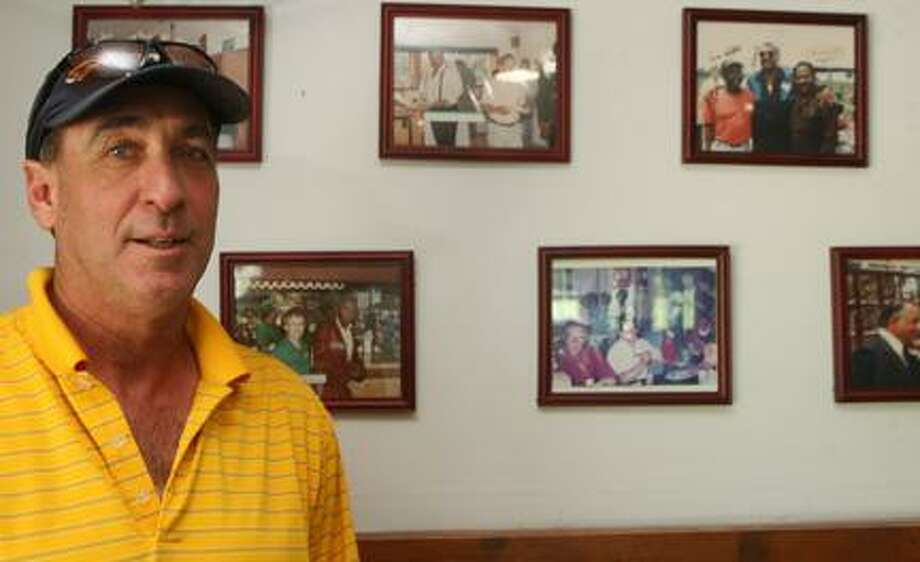 JOHN HAEGER @ONEIDAPHOTO ON TWITTER/ONEIDA DAILY DISPATCH Rick Quick poses in front of pictures of boxers at Casolwood Golf Course.