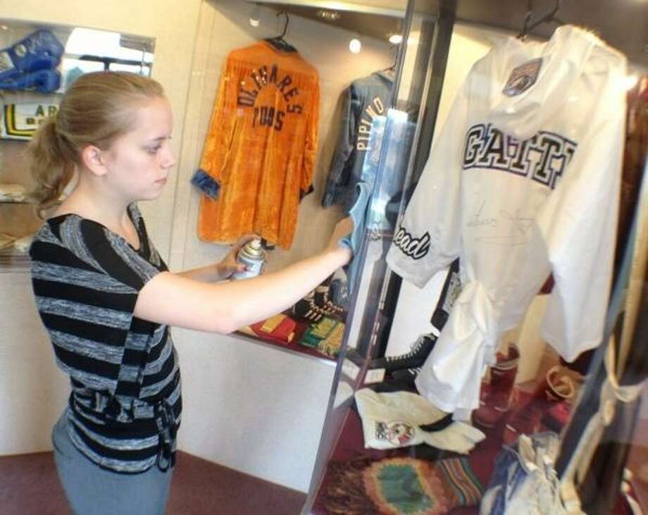 JOHN HAEGER @ONEIDAPHOTO ON TWITTER/ONEIDA DAILY DISPATCH Samantha McCarthy wipes down the display case with holds International Boxing Hall of Fame 2013 Inductee Auturo Gatti robe on Monday, June 3, 2013 at the Hamlin Canastota.