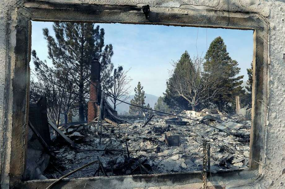A window frames the view of a home damaged by wildfires in Lake Hughes, Calif., early Sunday, June 2, 2013. Erratic wind fanned a blaze in the Angeles National Forest to nearly 41 square miles early Sunday, after fast-moving flames triggered the evacuation of nearly 1,000 homes in Lake Hughes and Lake Elizabeth, officials said. (AP Photo/Reed Saxon) Photo: ASSOCIATED PRESS / AP2013