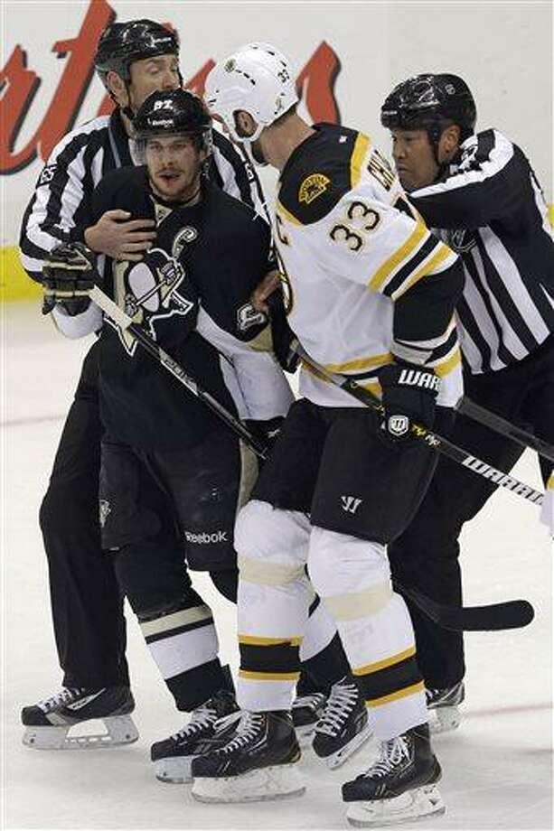 Linesmen separate Pittsburgh Penguins' Sidney Crosby (87) and Boston Bruins' Zdeno Chara (33) during the first period of Game 1 in an NHL hockey Stanley Cup Eastern Conference finals in Pittsburgh, Saturday, June 1, 2013. (AP Photo/Gene J. Puskar) Photo: AP / AP