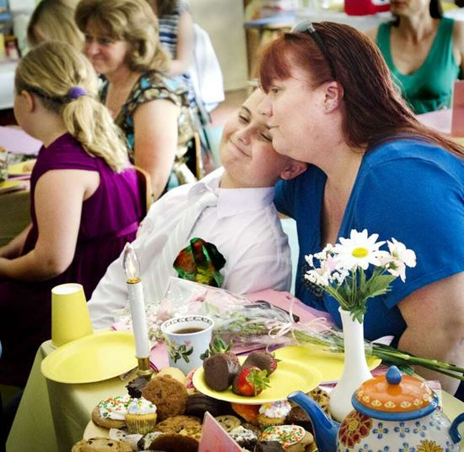 Milford-Ryan Lugo leans against his mother, Serena Lugo during a ppoetry reading at the St. Mary's 3rd grade Mother Tea.   Melanie Stengel/Register