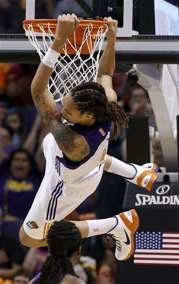 Phoenix Mercury's Brittney Griner hangs on the rim after making a two-handed dunk against the Chicago Sky in the second half during a WNBA basketball game on Monday, May 27, 2013, in Phoenix. The Sky defeated the Mercury 102-80. (AP Photo/Ross D. Franklin) Photo: AP / AP