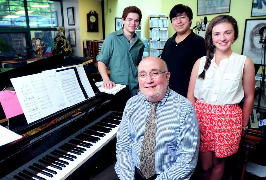 Hamden Hall Country Day School music teacher Louis Negri (bottom) is surrounded by a few of his students, (left to right) Robert Williamson, Libai Jordan and Allie Izzo, at the school's music chorale suite on 5/30/2013.Photo by Arnold Gold/New Haven Register   AG0500D