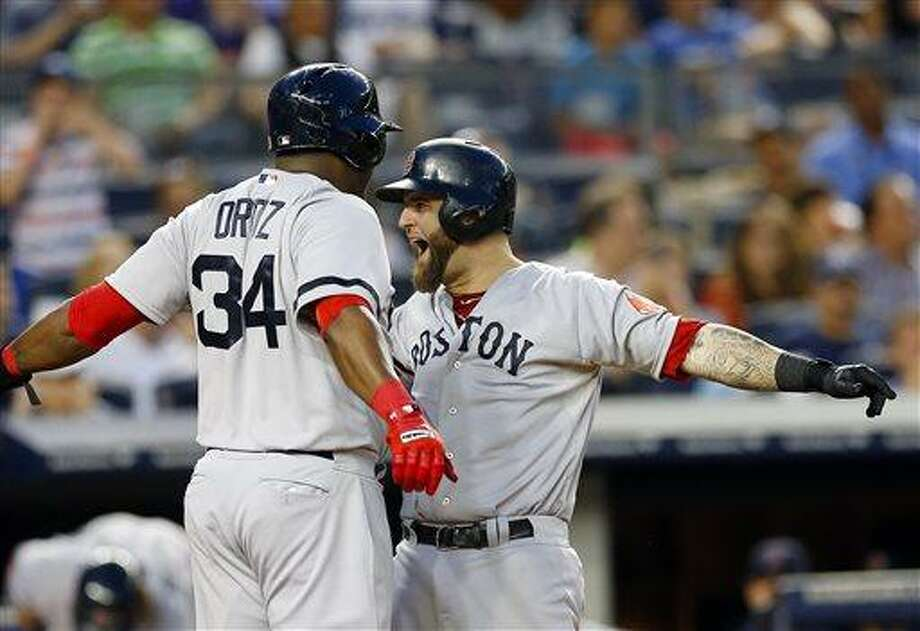 Boston Red Sox David Ortiz (34) greets teammate Mike Napoli at the plate after Napoli cleared the bases with a grand slam in the third inning of a baseball game against the New York Yankees at Yankee Stadium in New York, Saturday, June 1, 2013. (AP Photo/Paul J. Bereswill) Photo: AP / FR168017 AP