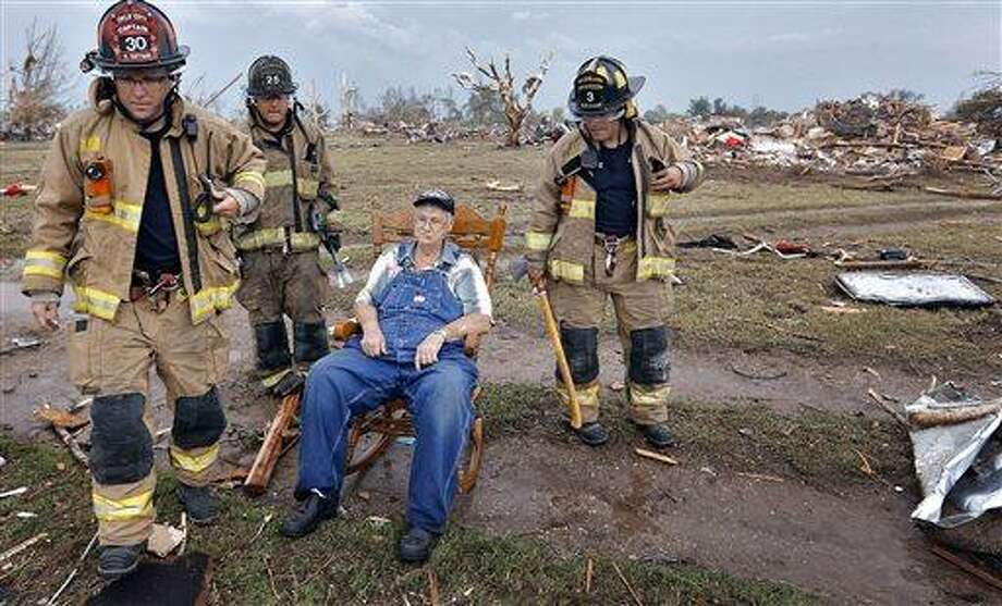 Oklahoma City fire fighters check on the status of Gene Tripp as he sits in his rocking chair where his home once stood after being destroyed by a tornado hit the area near 149th and Drexel on Monday, May 20, 2013 in Oklahoma City, Okla.  (AP Photo/The Oklahoman, Chris Landsberger) Photo: AP / 2013 AP