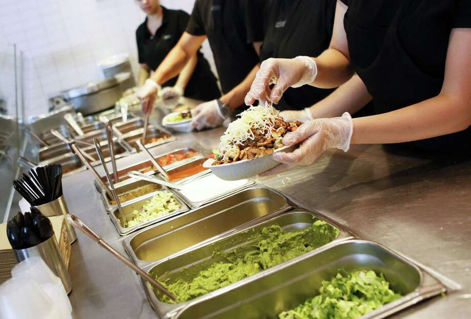 Employees prepare orders for customers at a Chipotle restaurant in Hollywood on July 16, 2013.Keep going for a look at the health code violations that have hit Houston-area Chipotles. Photo: Bloomberg Photo By Patrick T. Fallon. / 2013 Bloomberg Finance LP