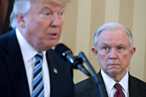 Attorney General Jeff Sessions (right) listens as President Donald Trump speaks at Sessions' swearing in ceremony in the White House on Feb. 9, 2017.