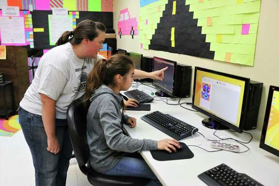 Computer graphic arts teacher Melissa Waller shows her seventh-grade student Emalee Villarreal how to do an 8-bit pixel art project in Microsoft Paint. The 32-year-old graphic-editing program is officially marked as deprecated, meaning it will be in the fall update but is no longer being actively updated and could be phased out at some point. It's unclear when Microsoft will officially remove Paint from its software.
