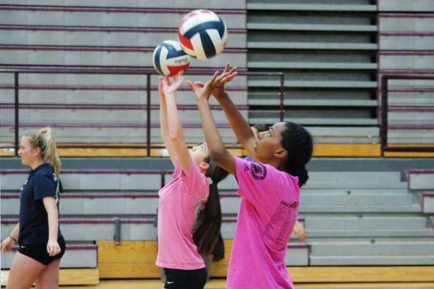 Tia Collins and Julie Thomas practice their setting skills at Pearland summer volleyball camp Tuesday, Jul. 25.