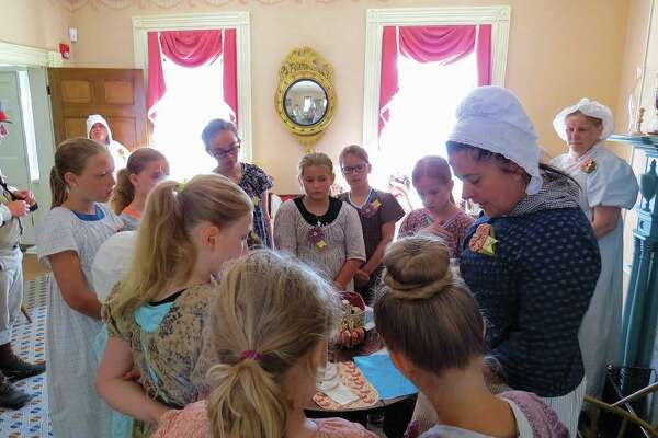 Twelve girls spent part of last week learning about life in the 1800s in Miss Lucy's Camp at the Col. Benjamin Stephenson House. Each girl wore a period dress and learned skills that girls living in the 1800s would have mastered, such as watercolor painting and sewing. Here, they listen to Stephenson House Director RoxAnn Raisner as she explains a sewing project.