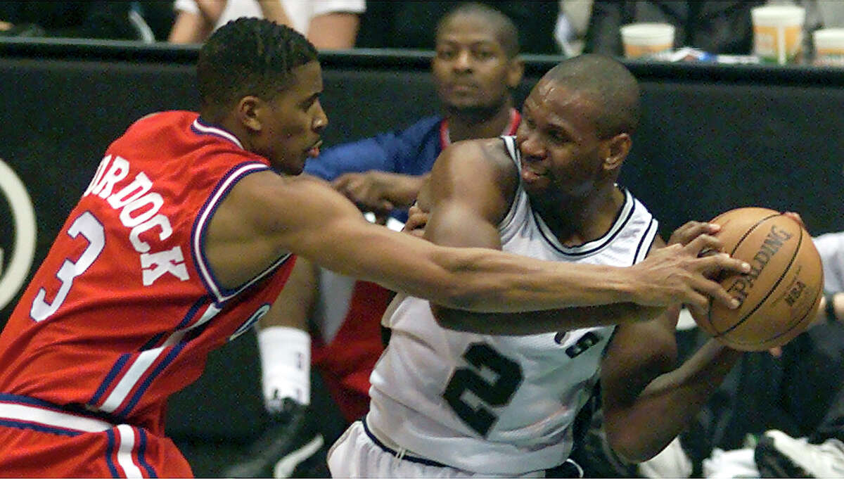 SPORTS - Spurs' Jaren Jackson (02) keeps the ball away from Los Angeles' Eric Murdock in the second period on Tuesday, January 25, 2000. Kin Man Hui/staff.