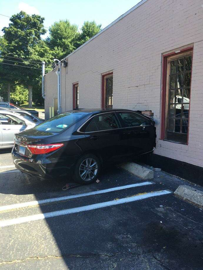 A car crashed into a building at Styles Salon 940 Boston Post Road in Milford on Wednesday. No one was injured. Photo courtesy of the Milford Police Department. Photo: Contributed