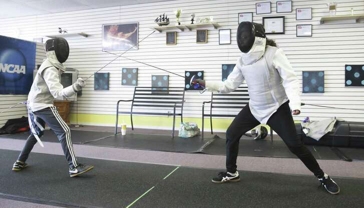 """Anna Marie Lopez (right) fences against opponent James Murphy as she works out at the San Antonio Phoenix Fencers' Club. After surgery to remove a brain tumor left her with multiple medical issues, she took up fencing to return """"strength and courage"""" to her life."""