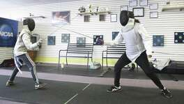 "Anna Marie Lopez (right) fences against opponent James Murphy as she works out at the San Antonio Phoenix Fencers' Club. After surgery to remove a brain tumor left her with multiple medical issues, she took up fencing to return ""strength and courage"" to her life."