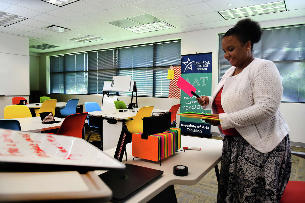 Latoya Lewis, director of the Associates of Arts in Teaching program at Lone Star College Tomball (LSC-Tomball) and a teaching fellow and instructor in the TEaCH lab, works in a mock classroom created at the campus to help new teachers learn with new technology and includes colorful dry-erase paddle boards and dry-erase boards that can be attached to the edge of a desk and used as a partition during test taking.