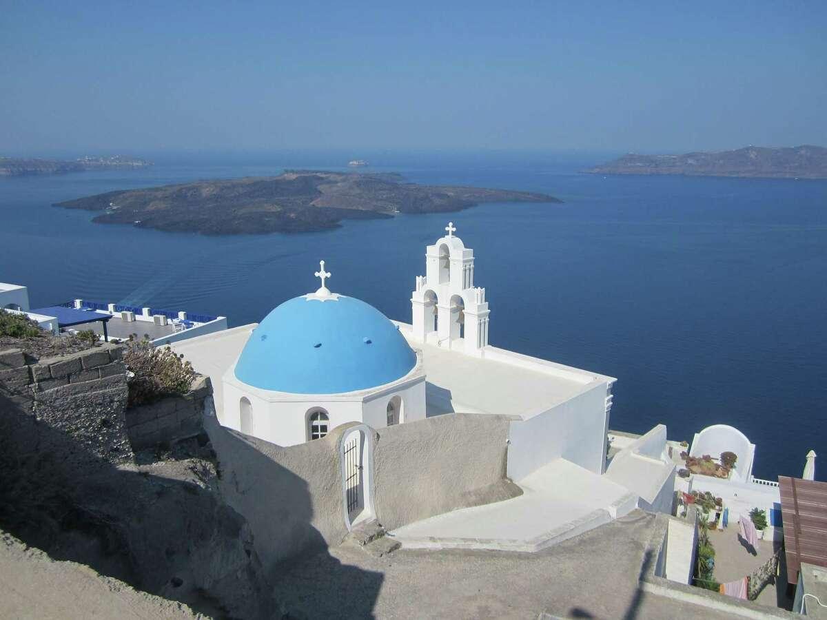 A blue-domed church building near Thira on the Greek island of Santorini overlooks the volcano isle known as Nea Kameni.