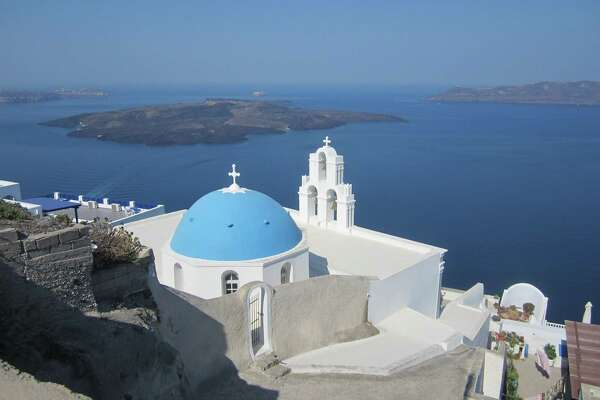 A blue-domed church building near Thira on the Greek island of Santorini overlooks the volcano isle known as Nea Kameni.