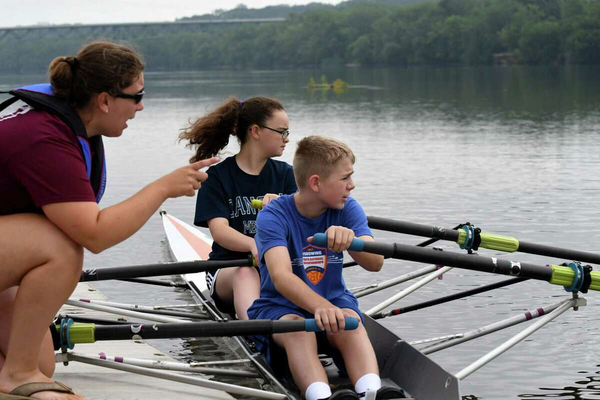 Rowing instructor Ashley Clary, left, gives guidance to Shannon Turley, center, and Joe Toomey, right, during an Albany Rowing Center junior summer camp at the Corning Preserve boat launch on Wednesday, July 26, 2017, in Albany, N.Y. The four-day sessions for boy and girls who have finished 7th grade is $200, and runs through mid-August.  (Will Waldron/Times Union)