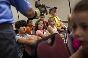 Children react to seeing an eastern screech owl up close during the Birds of Prey presentation by the Wildlife Recovery Association held at the Greendale Senior Center in Shepherd on Wednesday, July 26, 2017.
