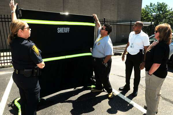 Members of the Bridgeport Police Department examine a section of portable barrier designed to hide victims of fatalities from public view during a demonstration at police headquarters, in Bridgeport, Conn. July 26, 2017.