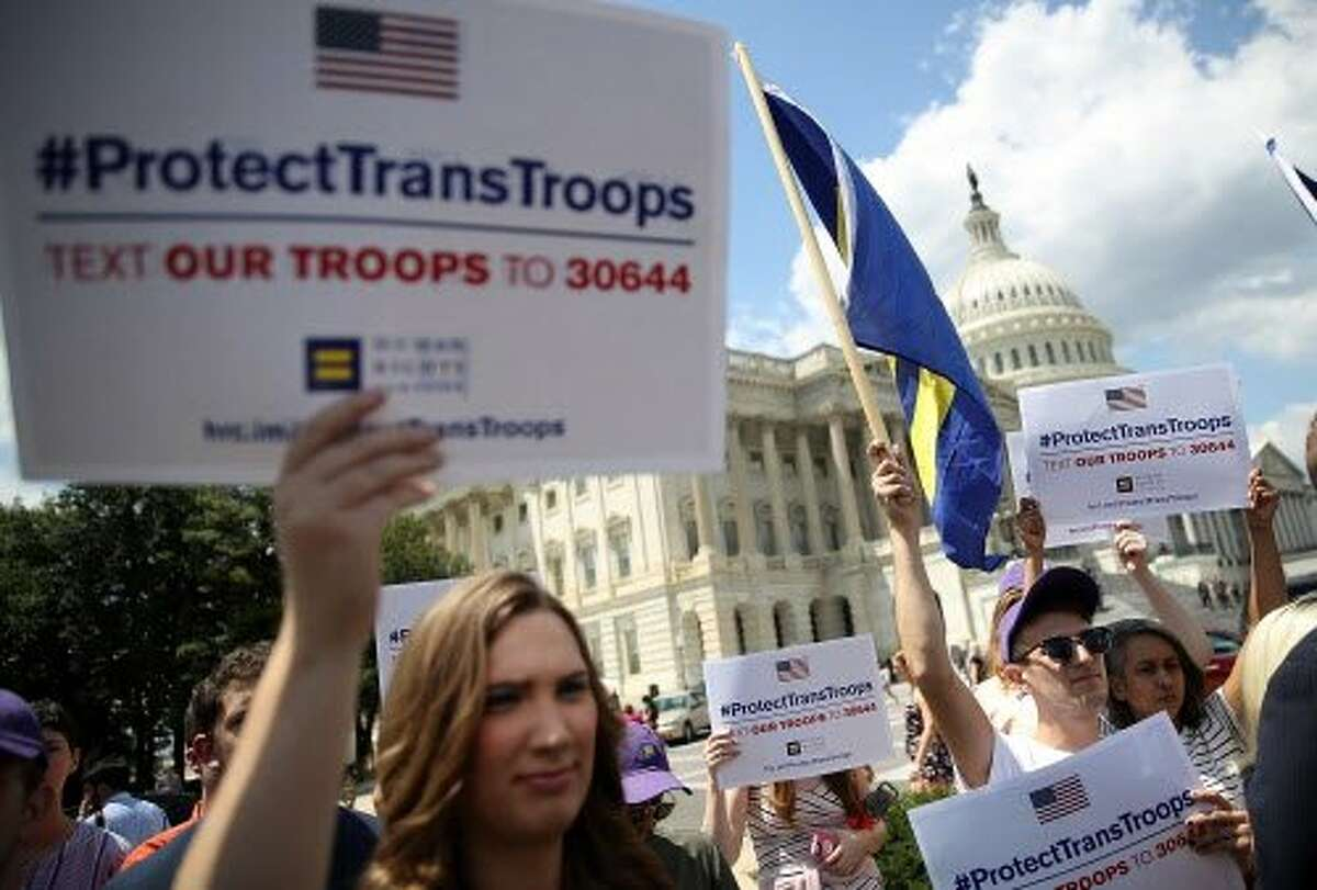 Gay rights supporters hold signs during a press conference at the U.S. Capitol condemning the new ban on transgendered servicemembers on July 26, 2017 in Washington, DC.