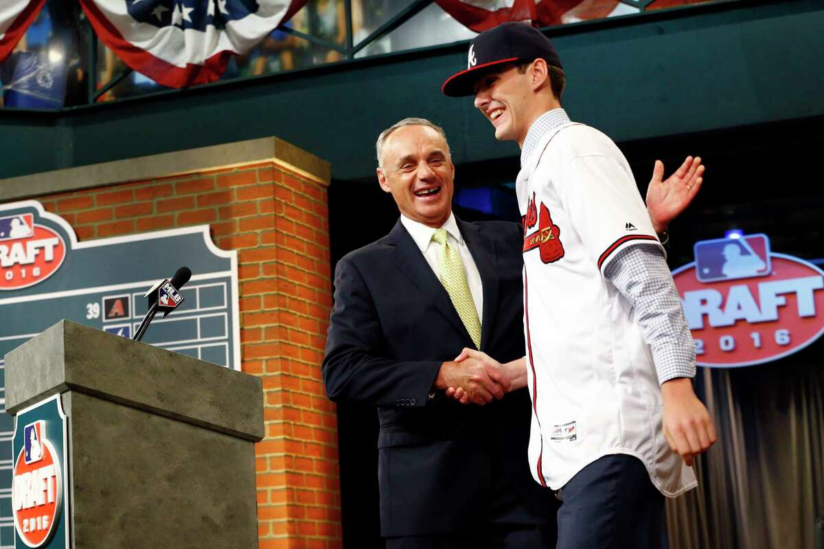 Baseball Commissioner Rob Manfred, left, shakes hands with Ian Anderson, a pitcher from Shenendehowa High School in Clifton Park after Anderson was selected with the third pick in the first round by the Atlanta Braves during the baseball draft, Thursday, June 9, 2016, in Secaucus, N.J.