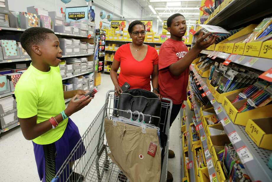 Laura Solomon shops for school supplies with sons Eric, 12, and Ke'Shawn, 15. She says she'd rather pay extra than get stuck in long lines on tax holidays.    Laura Solomon shops for school supplies with sons Eric, 12, and Ke'Shawn, 15. She says she'd rather pay extra than get stuck in long lines on tax holidays. Photo: Melissa Phillip, Staff / © 2017 Houston Chronicle