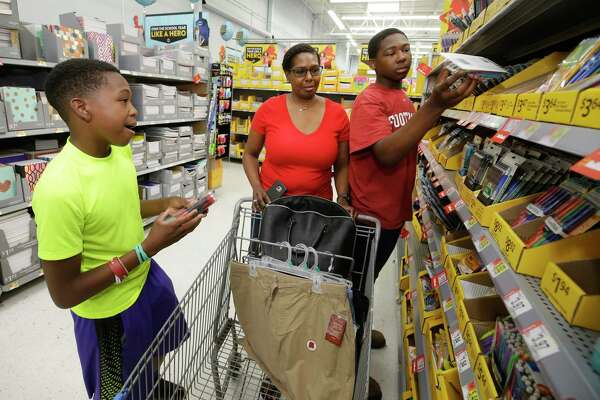 Seventh grader, Eric Solomon II, 12, left, and his brother, Ke'Shawn, 15, right, a tenth grader, shop with their mother, Laura Solomon, of Houston for school supplies at Walmart Tomball, 22605 TX-249,  Tuesday, July 25, 2017, in Tomball. ( Melissa Phillip / Houston Chronicle )