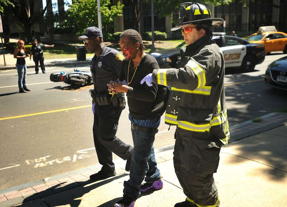 The bloodied victim of a scooter accident is escorted to a waiting ambulance outside 410 State Street in Bridgeport, Conn. on Wednesday, July 26, 2017. The accident occurred at aproximately 3 p.m. Photo: Brian A. Pounds / Hearst Connecticut Media / Connecticut Post