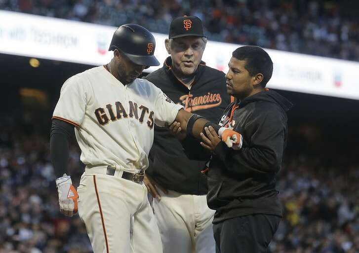 San Francisco Giants' Eduardo Nunez, left, is checked on by trainer Eric Ortega, right, and manager Bruce Bochy, rear, after being hit with a pitch against the Pittsburgh Pirates during the third inning of a baseball game in San Francisco, Tuesday, July 25, 2017. Nunez stayed in the game. (AP Photo/Jeff Chiu)